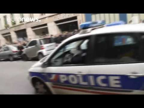 Paris protesters set police car on fire with 2 officers inside
