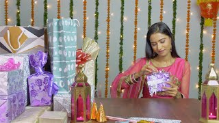 A young attractive woman happily opening  her Diwali gifts in traditional clothing
