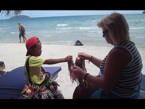 Khmer kid speaks English selling souvenir stuffs at the beach