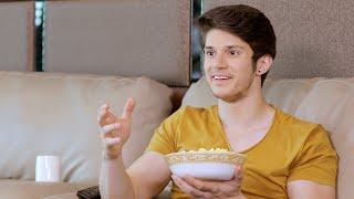 Mid shot of a young boy sitting on sofa and watching an interesting movie while eating popcorn