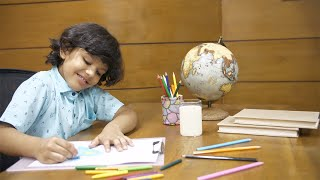 Young innocent child doing his art homework very happily - creative little artist at work