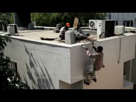 Workers paint the outside of a building in India : risky business