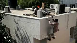 Workers Painting The External Wall Of A Building In India