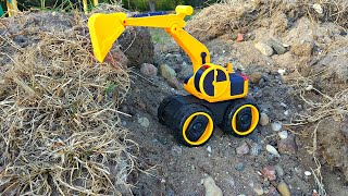 Экскаватор роет землю ковшом и загружает ее Трактору в прицеп. Видео для детей