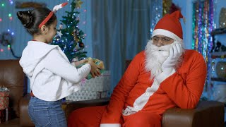 A young innocent kid giving a Christmas present to an unhappy Santa Claus in India