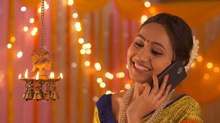 Indian beautiful woman talking on the phone beside diya- Diwali scene at home
