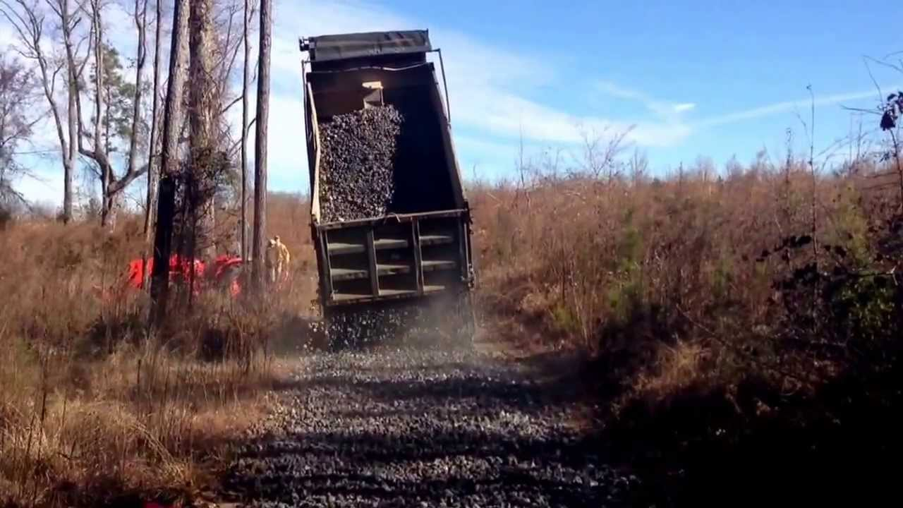 Dump truck with straight pipe spreading rock - YouTube