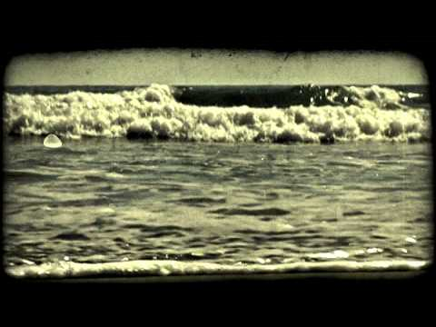 Waves cover beach. Vintage stylized video clip.