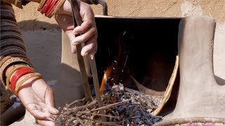 Village life in India - Indian woman cooking food on a traditional wood fire stove / chulha