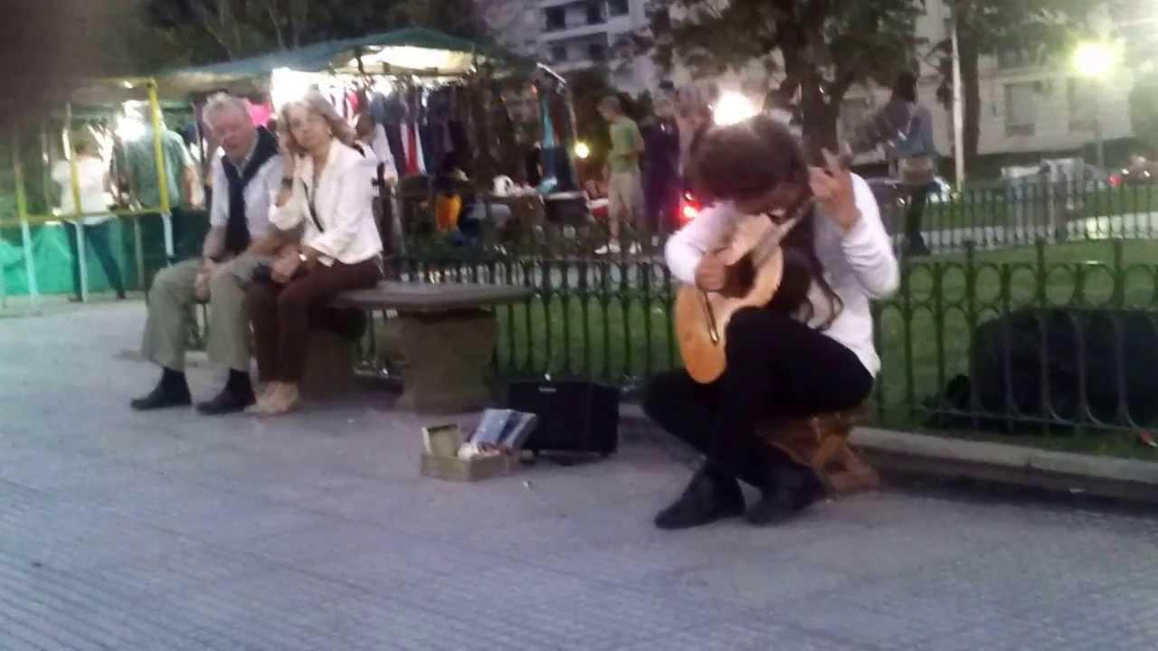 Artista callejero tocando la guitarra en Recoleta