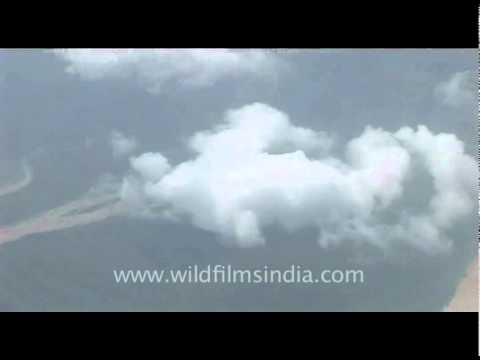 Flying over monsoon-filled river through cloudy skies, into Kathmandu airport