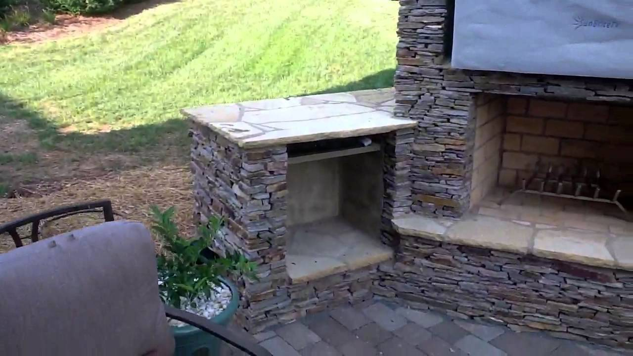 stack stone outdoor fireplace and outdoor kitchen with sunbrite tv