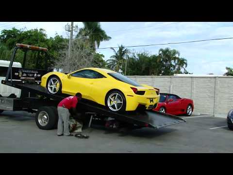 yellow Ferrari 458 Italia being loaded on a tow truck