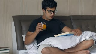 Young college student reading a book while sitting in his bed - lifestyle concept
