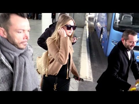 EXCLUSIVE: Gigi Hadid arriving in Paris with Zayn Picture on her phone