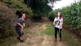 Sweaty boy gets butt kicked against small white girl in corn-stalk sword-fighting competition