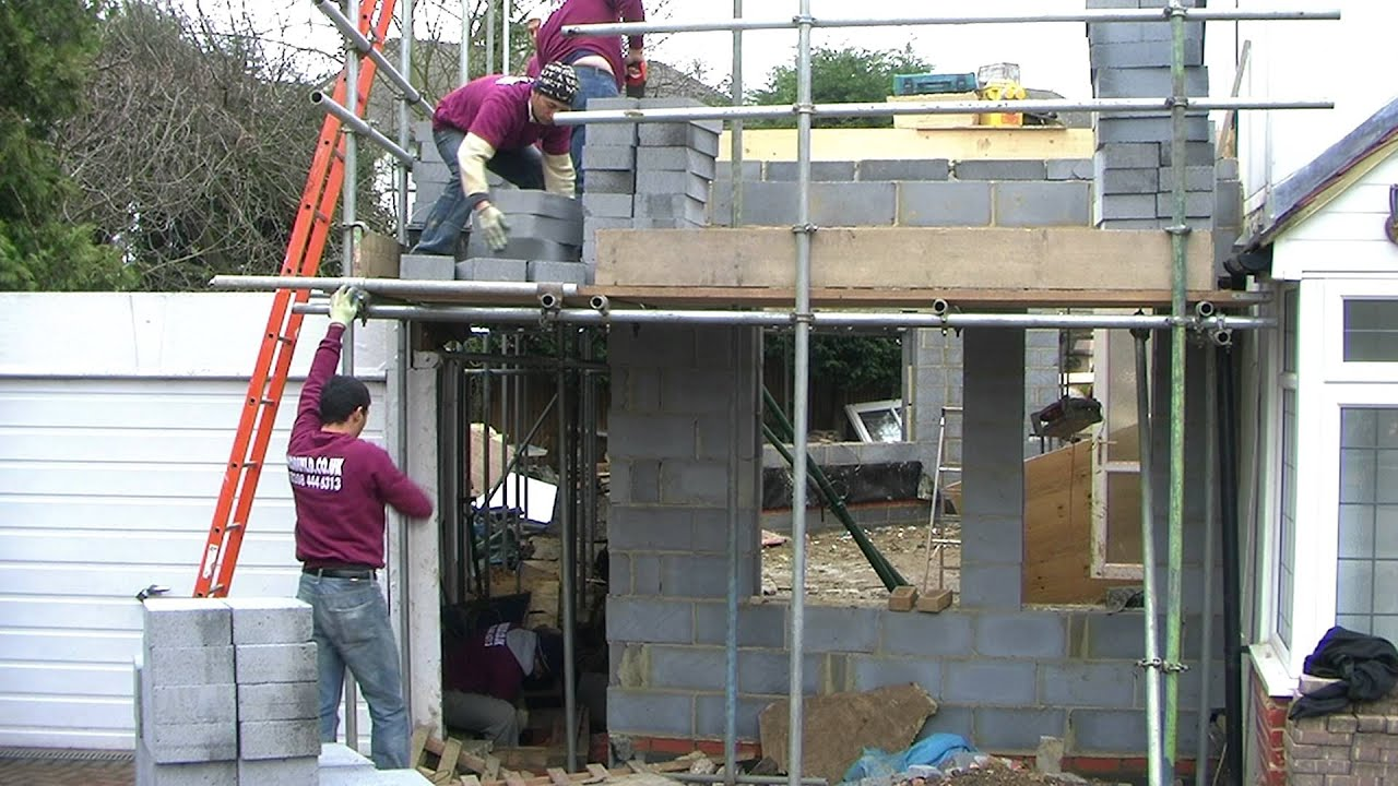 Bricklayers building a two storey house extension in for How to build a 2nd story floor