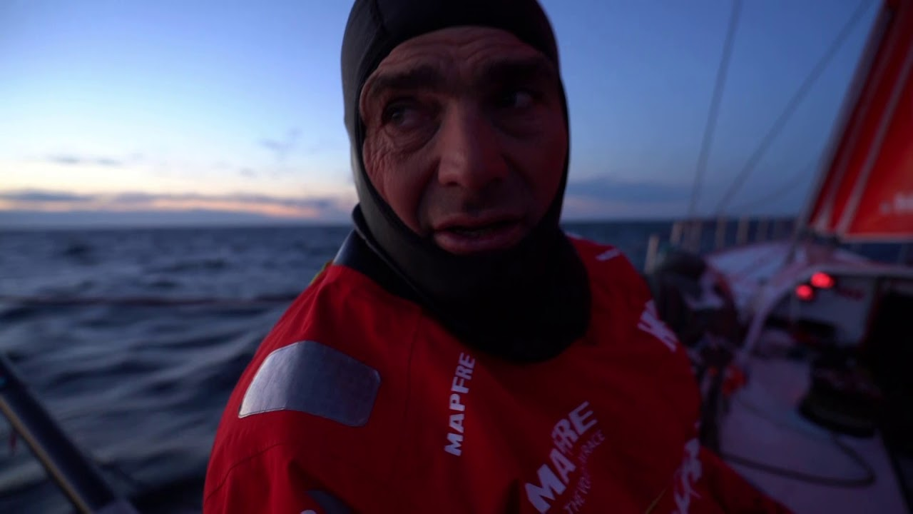 Xabi, heading south in the pre-dawn, talks in Spanish about Dongfeng, Vestas, and Brunel. He repeats in English: Just going through the first night here, even if it doesn't look like it, 3:30 local time. After a not very good start of the day we've recovered quite well. Just passed the waypoint for Norway 2 hours ago. Now going downwind to Arrhuus. We were second there a half mile behind Dongfeng, and Brunel is a couple of boats behind, 8 miles upwind. It's going well. Hopefully we can get in front of Dongfeng soon. We see them rounding the buoy and deploying the A3, then see it again from the stern cam. Dongfeng on the bow ahead of them. Small powerboat alongside. Sophie bagging the J1. Dongfeng ahead and to starboard. Night vision shots of the crew on the bow, in the cockpit. Xabi talks with Sophie; trims the main.