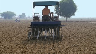 Indian farmer plowing his agricultural land with the help of a tractor - farming concept