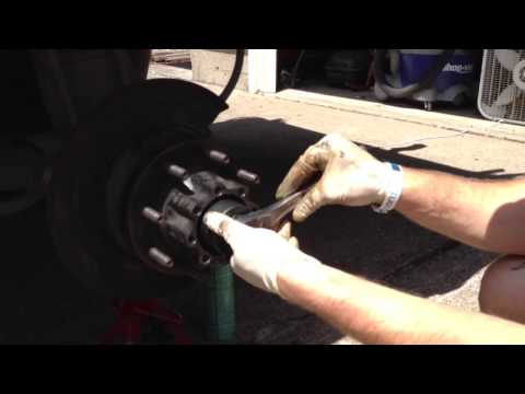 Removing rear left axle locking nut.