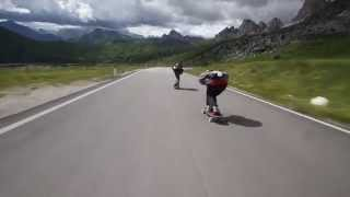 Crazy downhill skateboarders flying by cyclists