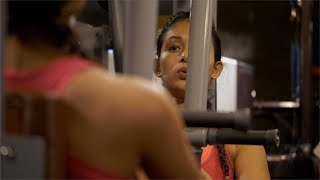 Reflection of a sporty Indian girl strenuously working out at the gym - fitness concept