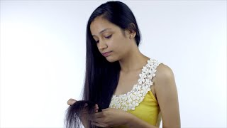A young girl holds her long hair looking at the damage - damaged hair concept