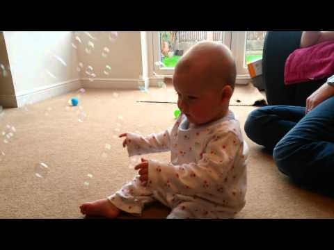 Baby laughing hysterically at irish setter dog