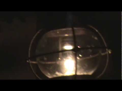 An Old Ship's Whale Oil Globe Lantern/Lamp Lit at Night In High Wind.
