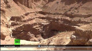 Новые свидетельства зверств ИГ: корреспондент RT увидел место захоронения тысяч жертв боевиков