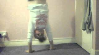 girl trying to do a handstand against a wall