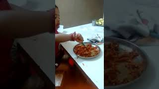 Cute little baby girl eating noodles funny
