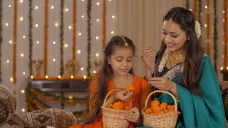 South Indian mother-daughter preparing flower garlands (mala) for Diwali Puja in traditional wear