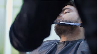 A hairdresser trimming beard of a young man in the men's hair salon