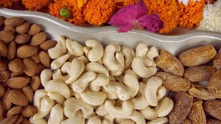 Pan shot of a silver dry fruits tray kept on a floral platform for Diwali celebration