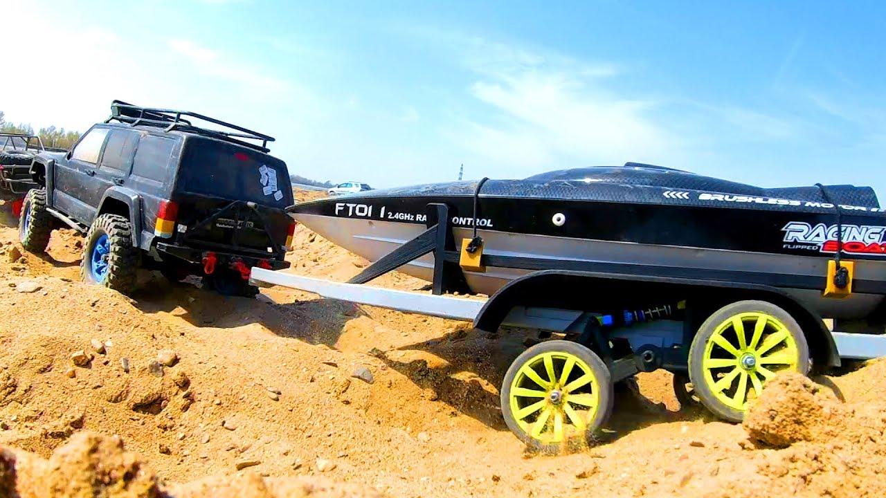 RC Car Jeep Cherokee тащит по песку катер на прицепе к воде