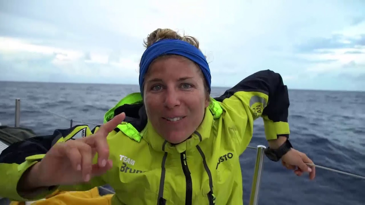 """Very high drone shot. Peter, shirtless below: Had a pretty good night last night. Can see the boats in front of us, Vestas and Dongfeng. Bouwe: How's the morning? Little clouds, a little rain. Shot of a gybe. Other boat to port. Nina: I have the craziest dreams offshore. I think it's because your sleep is broken up, all the gybing. They're really real. Sam asks Bouwe: When you're offshore, what do you dream about? Bouwe: Sex, with my wife. [To Capey: Isn't that true?] Capey, eating: I don't dream of sex with your wife. Nina: I had this really strange dream in the Southern Ocean. That the Volvo Ocean Race wasn't real; it was a coverup for a drug-smuggling operation... We're in an escape plane, and a missile is coming, and a tracker was in my bag... Sam asks Abby: How long is it until Neptune comes? Abby: Less than 24 hours. Bouwe: Three. Here, here, and here. (He demonstrates a triple reverse mohawk.) Abby: I dream about my kid. I think when you get so tired you start to hallucinate. She asks Bouwe what his dreams are about, and he repeats the """"sex with my wife"""" line. Abby laughs. """"That was honest."""" Low drone shot circling the boat under clouds. Abby, at night in black and white: We are either just passing or about to pass Turn the Tide on Plastic. Shot of them to port. Carlo: The other day I had a nightmare. I went to this fishing farm, where they were breeding salmon. I went inside and I was being chased by the fishermen that were working in there. But they had fish skin and it was melting. It was really strange. Peter on the helm. Carlo: Just lost a little bit on them. Louis: I've had many crazy dreams, but they're too crazy to share. Peter: I'm always pretty tired for some reason. Shot of Kyle sleeping below with the engine running."""