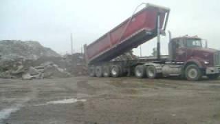 a quad axle lead trailer dumping broken concrete