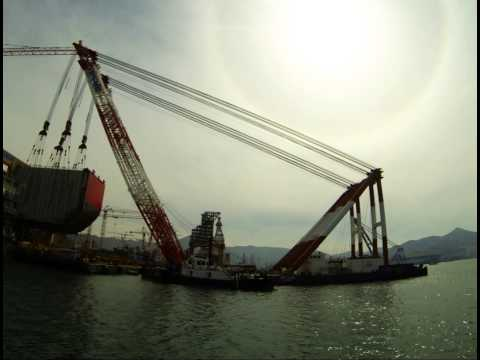 Floating crane lifting megablock at shipyard