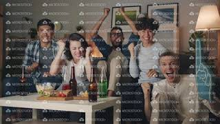 Slow motion portrait of excited students watching sports game on TV at night