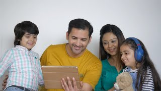 Indian family happily using a digital tablet while sitting together on a couch - weekend fun