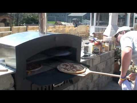 wood pizza oven cooking pizza in an outdoor wood fired pizza oven