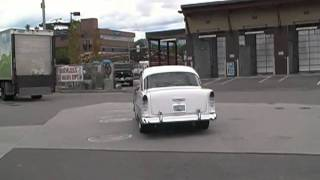 a manual 1957 chevorlet car starting up and driving off from a chevron gas station kelowna bc