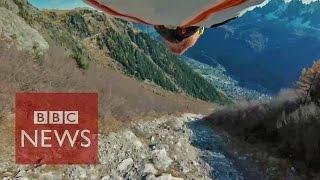 Amazing 'high five' by wingsuit pilot