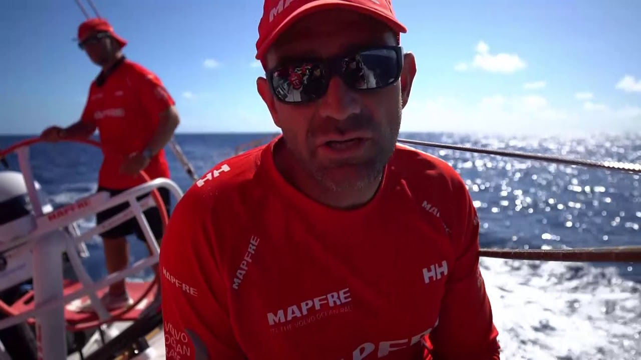 Joan talks on deck: yesterday had big showers, had to take a few of them on starboard, and ended up left of the rhumb line. Got passed by Vestas and Turn the Tide. In a group of four boats with Dongfeng ahead. Xabi recaps the same events in Spanish. They're especially concerned about Dongfeng because of how close they are in the standings. Shot looking forward as they sail to weather on port under the J1. Rob on the helm. Pablo trimming. Shifting the stack to leeward in preparation for tacking. Then we see the tack. Tamara grinding. spreader cam view of the deck with the J1 flying. Night-vision shots with rain. Night-vision shot of the bow with spray coming over.