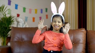 Pretty Indian girl waving her hands in a cute bunny hairband - lifestyle kids