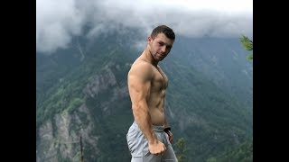 Handsome boy showing muscles in mountains