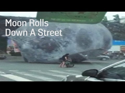 Watch A Moon Balloon Roll Over Cars