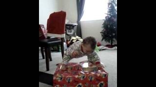 Funny Baby opening up Christmas gifts