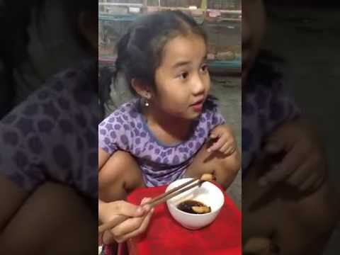 A little girl eats raw coconut worm